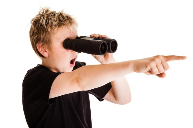 Teenage boy looking through binoculars and pointing with his finger